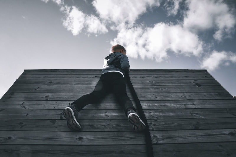Low angle view of man sitting on wood against sky