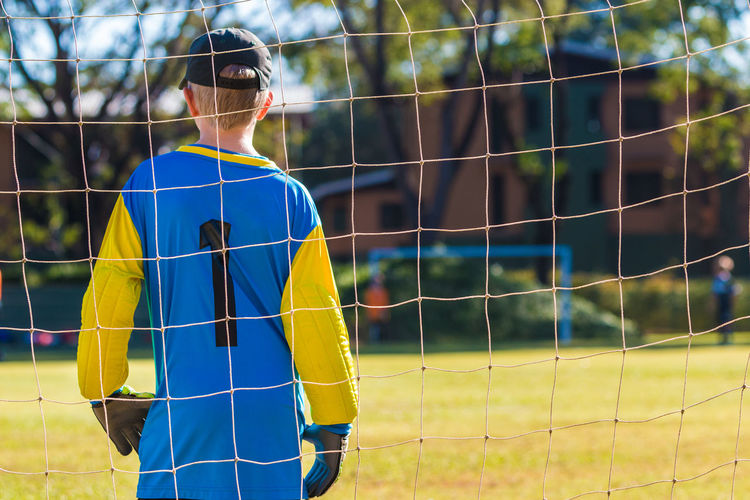 Rear view of boy standing on soccer field