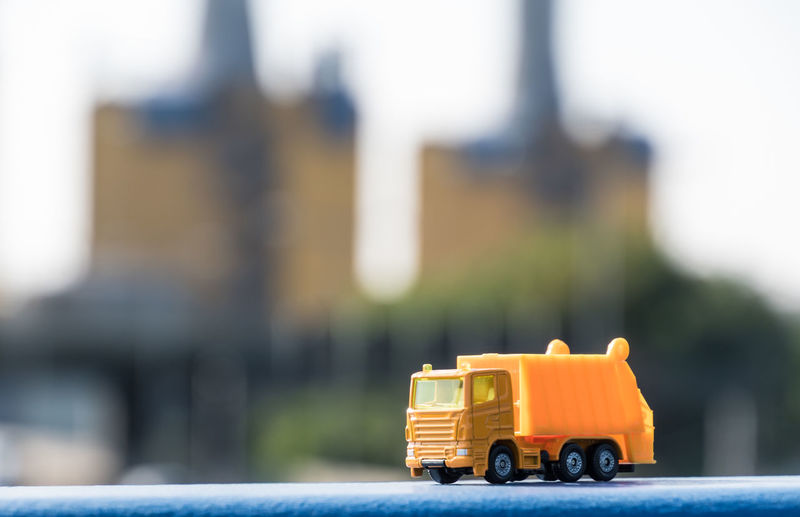 Close-Up Of Yellow Toy Truck On Railing