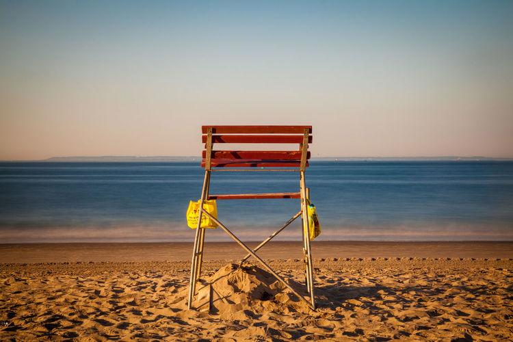 Empty lifeguard chair at beach against clear sky