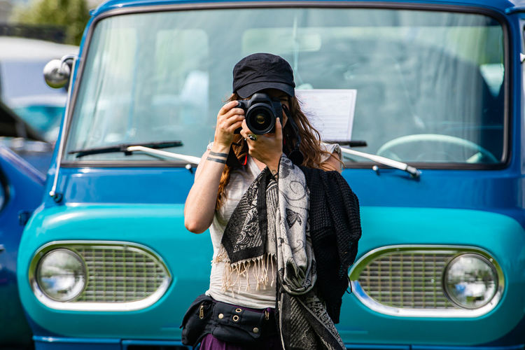 Young woman holding camera while standing against car