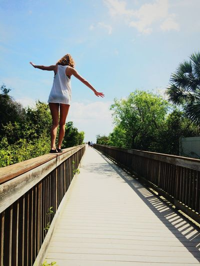 Rear View Of Woman Balancing On Boardwalk Railing