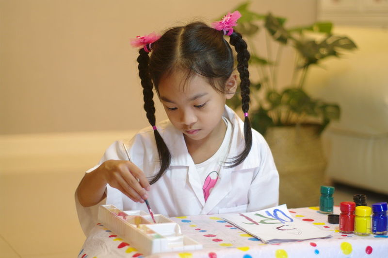 Portraits of cute asian girls playing and painting with joy