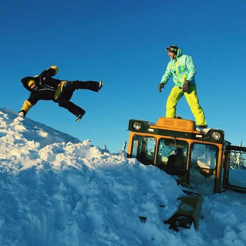 Low angle view of men enjoying in snow against sky