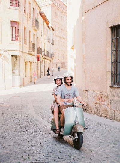 A couple riding a vespa through the city center. City Center Love Romantic SPAIN Travel Vespa Adult City Couple - Relationship Couple In Love Emotion Full Length Happiness Looking At Camera Men Plaza Positive Emotion Smiling Street Transportation Travel And Tourism Travel Destinations Two People