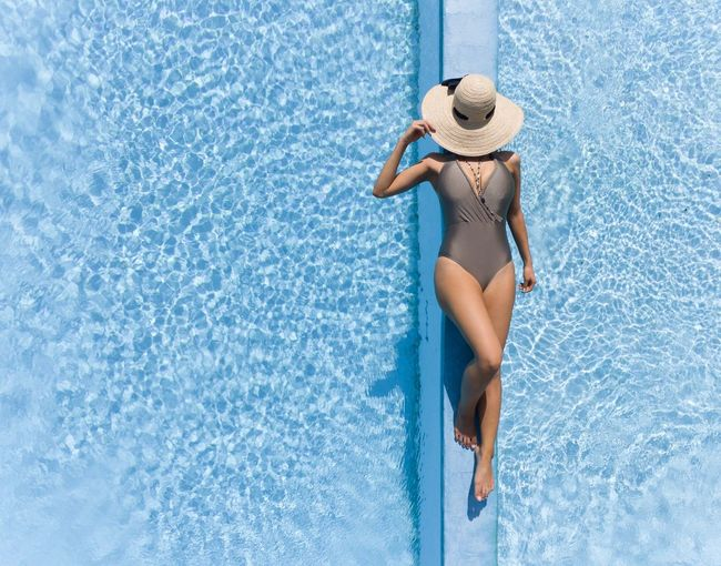 Swimming Pool Summer Hat Vacations Bikini Relaxation One Person Sun Hat Young Adult Adult Women Lifestyles People Water One Woman Only Outdoors Blue Only Women Beauty Day