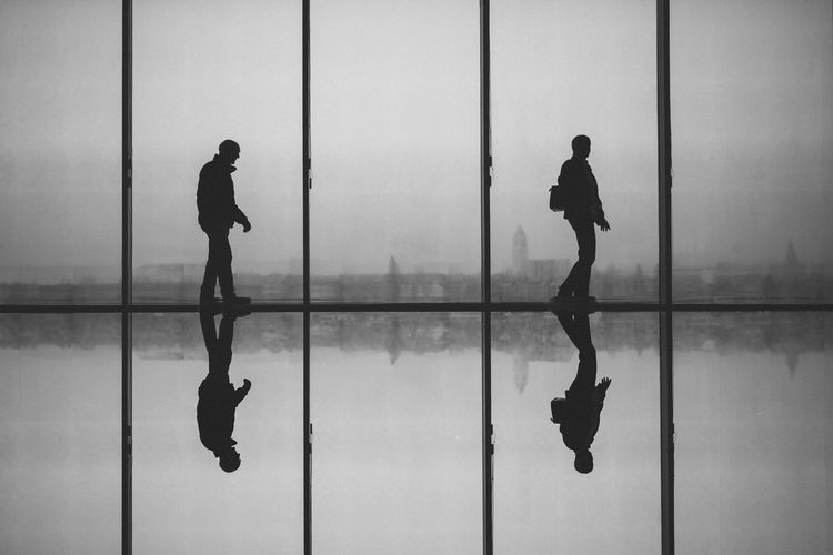 Silhouette Men Against Window With Reflection On Floor