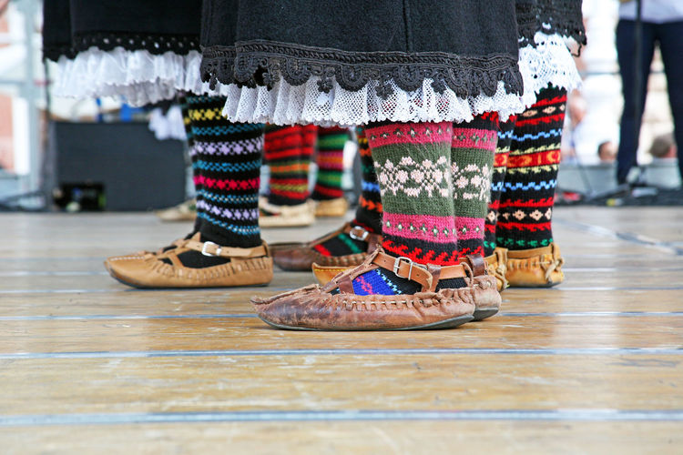 Low section of people wearing colorful socks and shoes