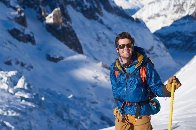 Man standing on snowcapped mountains during winter