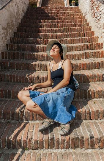 Summer travel Architecture One Person Brick Casual Clothing Staircase Real People Young Adult Outdoors Sitting Summertime Feeling Good Feeling The Sun Travel Destinations Traveling Far From Home FAR AWAY
