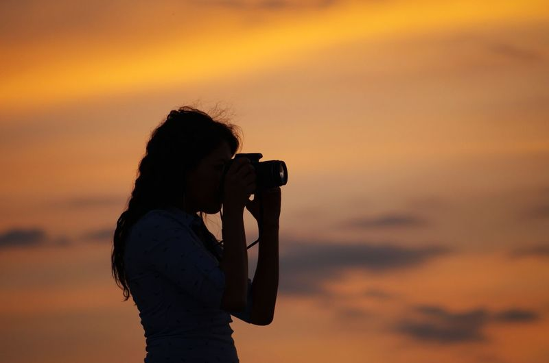 Side view of silhouette woman photographing against orange sky