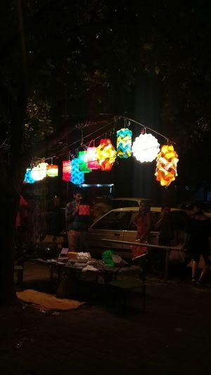 People in illuminated market at night