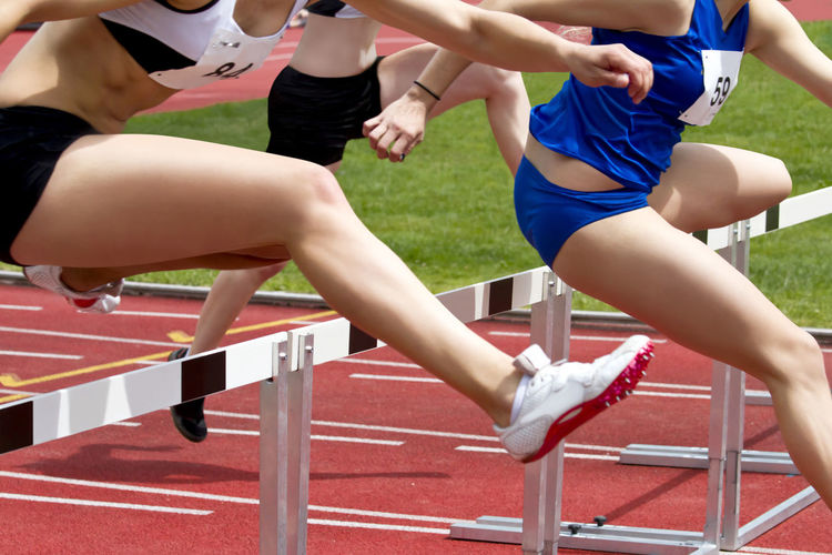 Low section of female athletes crossing hurdles