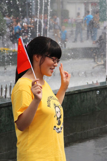 Chinese Flag Chinese Girl Adult Architecture Building Exterior Built Structure Casual Clothing Childhood Day Flag Focus On Foreground Leisure Activity Lifestyles One Person Outdoors People Posing Real People Standing Water Young Adult
