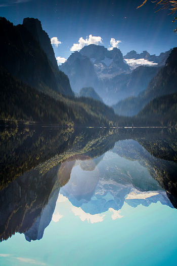 Scenic View Of Calm Lake With Mountains Reflection