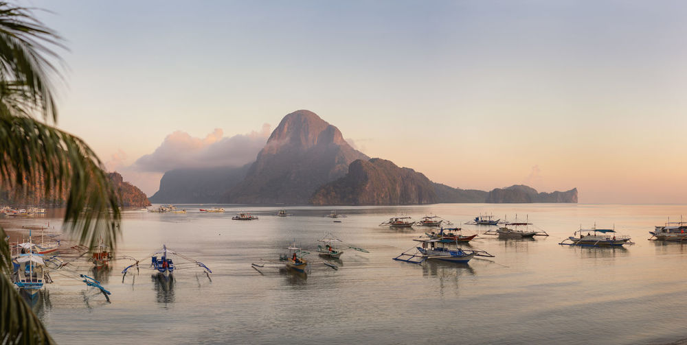 Boats in sea against mountains during sunset