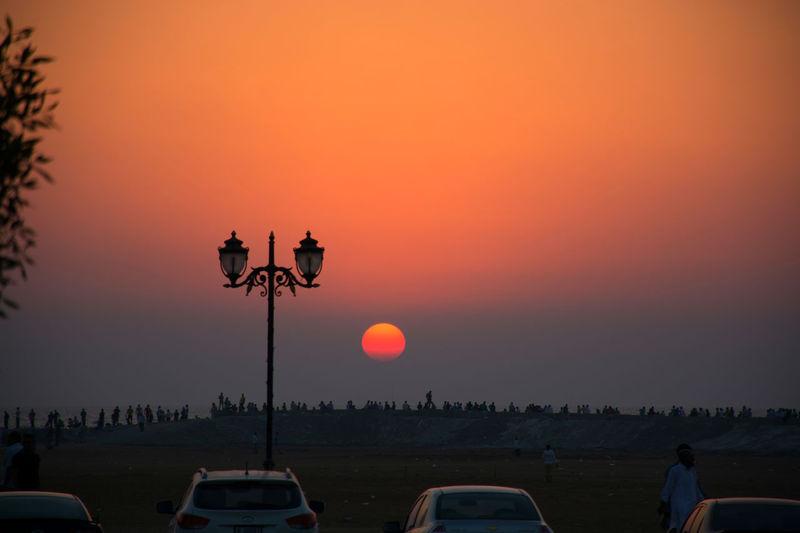 Cars in parking lot against orange sky
