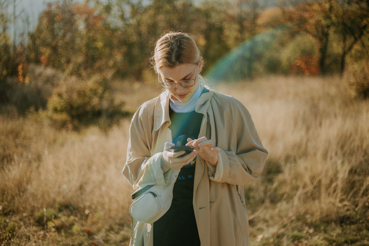 A young woman using her phone in a field during a sunny autumn day