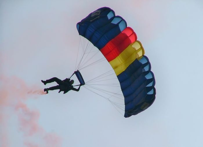 Low Angle View Of Man With Parachute And Smoke Against Sky