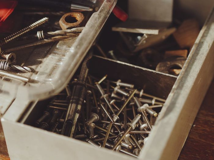 High angle view of rusty work tools in box at workshop