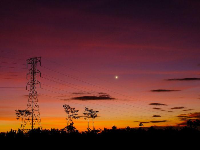 Silhouette electricity pylon against romantic sky at sunset