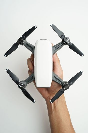 Cropped hand of woman holding drone against white background