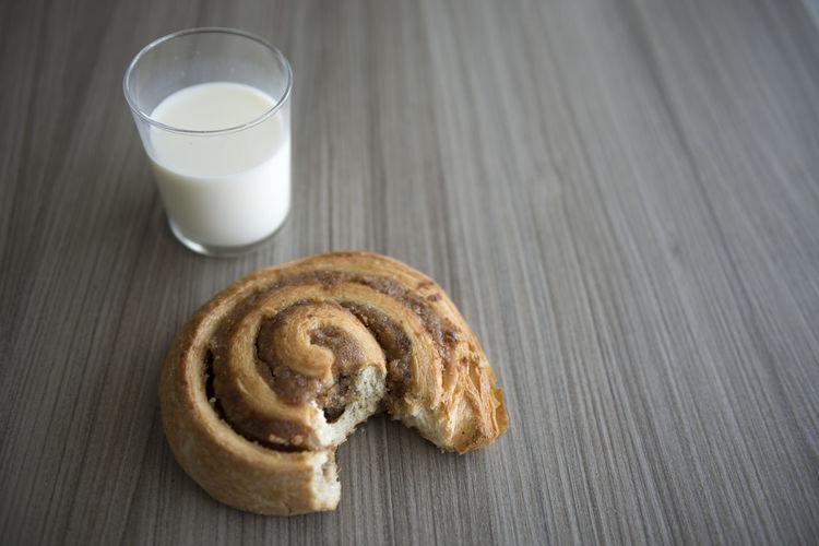 Glass of milk and eaten sweet bun on table