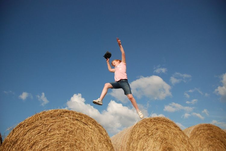 Low angle view of young woman jumping on hay bales against sky