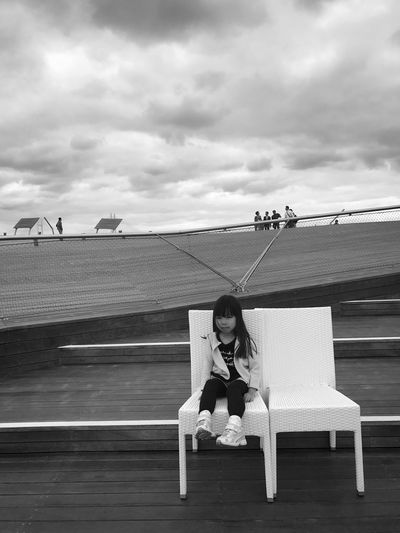 Girl sitting on seat against sky