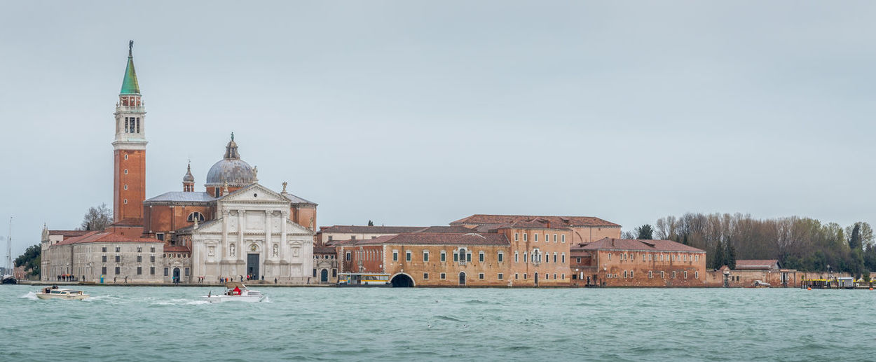 View of buildings by sea against sky