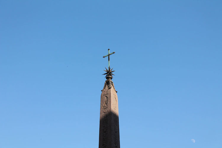 Low angle view of cross on pole against clear sky