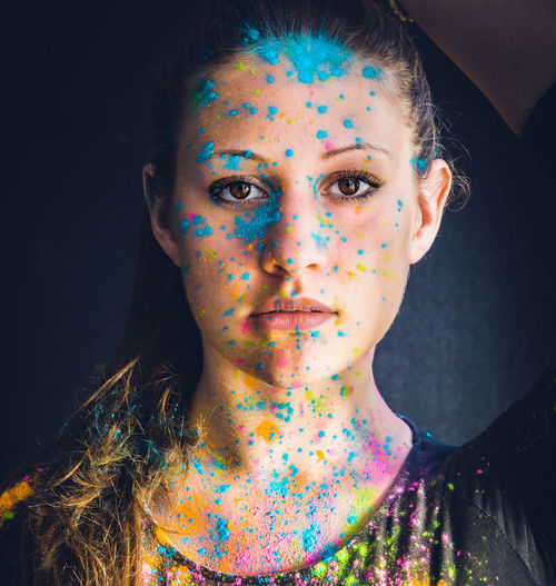 Close-up portrait of serious young woman face covered with colorful powder paint
