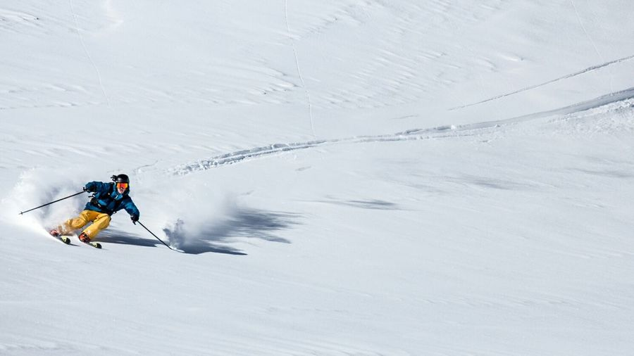 Tourist Skiing On Snow Covered Landscape