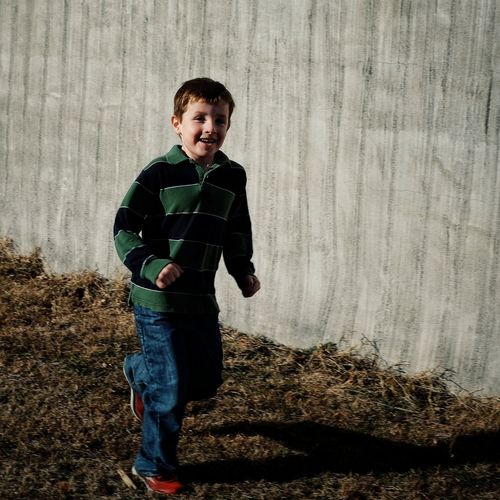 Portrait Of Smiling Boy Against Wall On Field