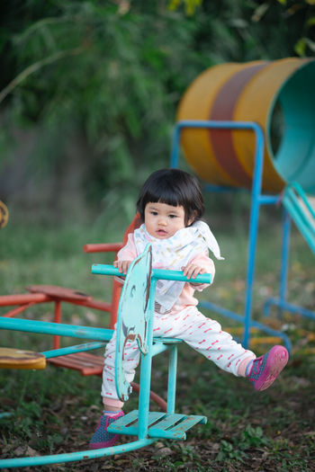 Cute girl looking away while sitting on equipment in playground