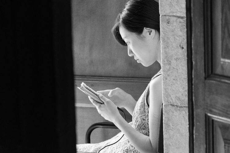 Side view of woman using phone while sitting at home