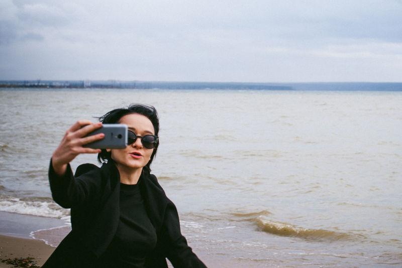Woman taking selfie through mobile phone at beach against sky