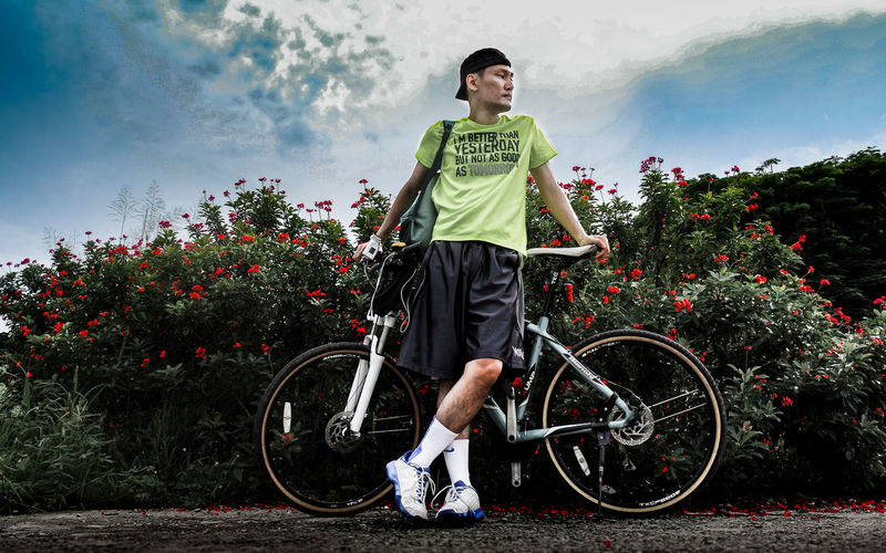 Full length of man standing on bicycle against sky