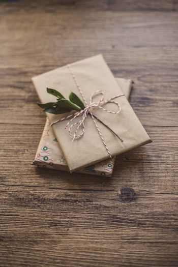 Wrapped gifts on wooden table Christmas Holiday Love Wrap Chritsmas Decoration Gift Paper Wrapped Celebration Tied Up Indoors  Ribbon Food And Drink High Angle View No People Christmas Present Food Ribbon - Sewing Item Tied Bow Day Freshness Still Life Wood - Material Table Close-up