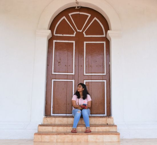 Full length of woman sitting at entrance of building