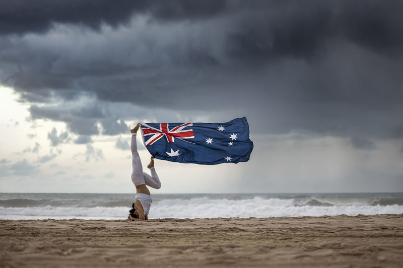 Woman holding flag while exercising on beach against sky