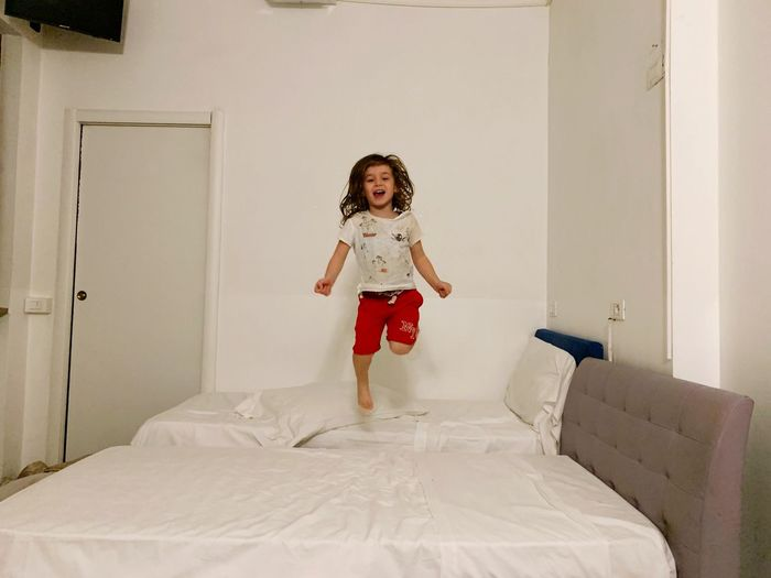 Child Childhood Full Length One Person Offspring Girls Portrait Indoors  Females Emotion Smiling Looking At Camera Furniture Domestic Room Front View Happiness Innocence Jumping Women Fashion
