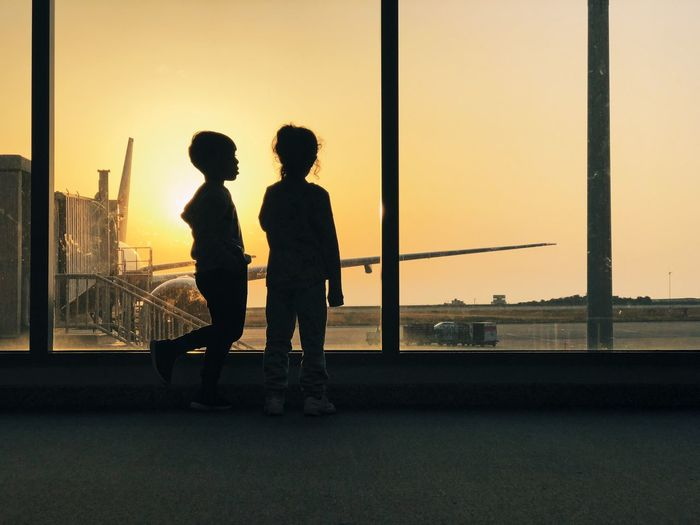Boy and girl against window at airport during sunset