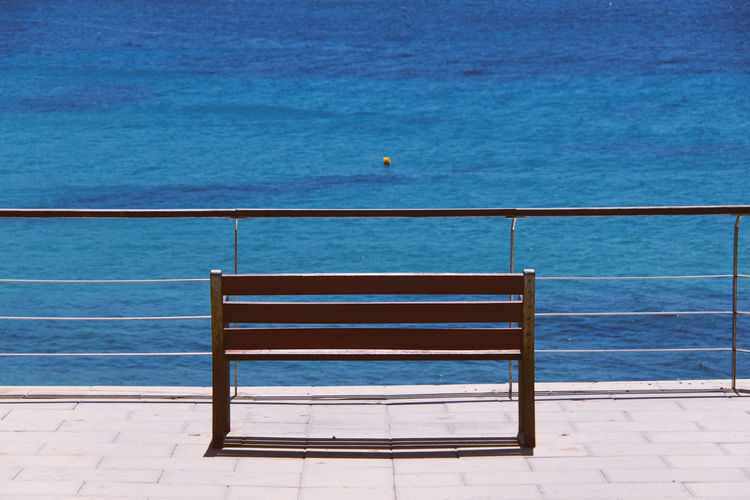 Empty Bench By Railing Against Sea