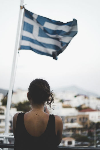 Rear view of woman standing against greek flag in city