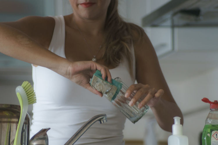 Midsection Of Woman Cleaning Drinking Glass In Kitchen