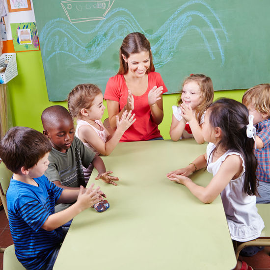 Mid adult teacher clapping while sitting with students in classroom at school
