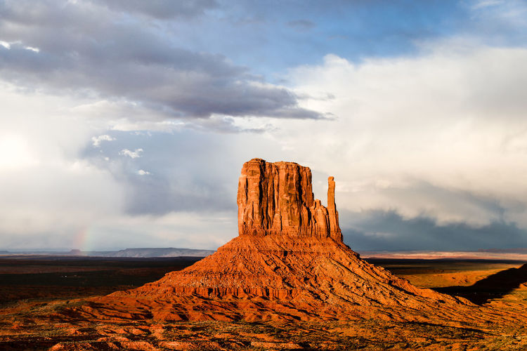 Rainbow at sunset in monument valley Monument Valley Travel Destinations Exploration Adventure Outdoors Sunset Golden Hour Arizona Utah Desert Beauty Desert Landscape Rainbow Dramatic Sky Clouds Cloudy Stormy Weather Storm Butte North America Natural Landmark Arid Climate Desert Wild West Rock - Object Eroded Physical Geography Natural Landmark Arid Landscape Rugged Geology
