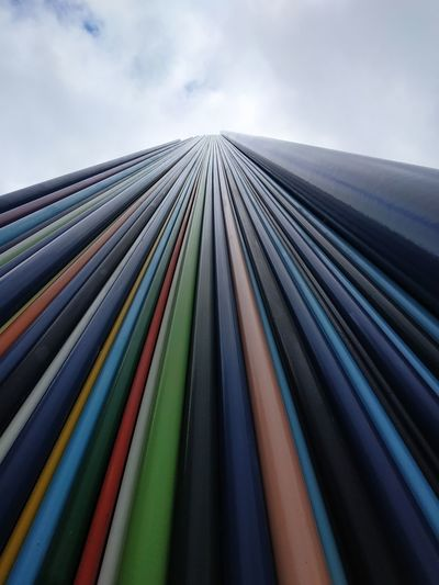 Low angle view of multi colored metallic structure against sky