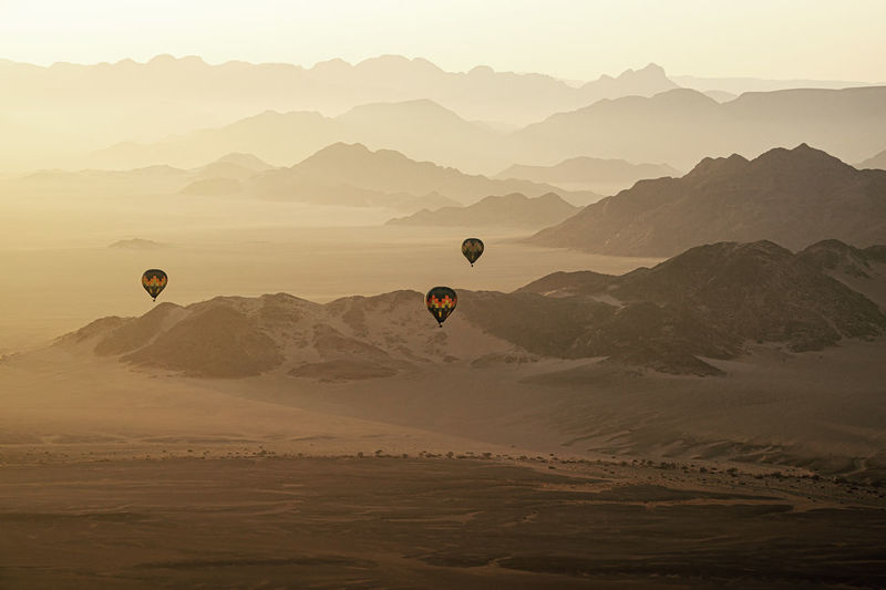 Hot air balloon flying over mountains against sky